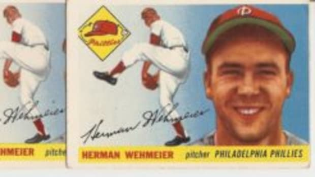 "The Wehmeier card on the right, with a missing dot over the ""i"" in his signature and an asterisk next to his lifetime stats on the back, also has a logo on the front that is slightly cut off on the left side."