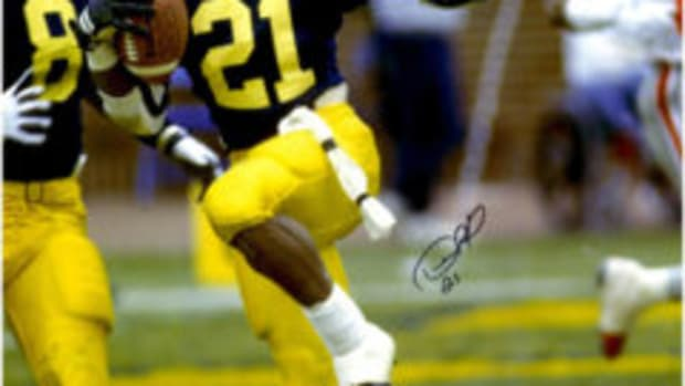 "Prior to winning the Heisman Trophy in 1991, Michigan's Desmond Howard struck the ""Heisman"" pose during a game against Ohio State. Autographed versions of the photo, like this one, are available through www.fansedge.com."