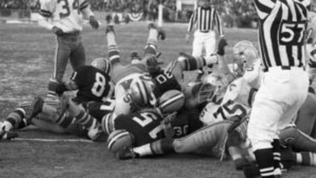 An official signals touchdown as Green Bay Packers quarterback Bart Starr (No. 15) plunges into the end zone for the winning TD in the 4th quarter of the NFL Championship game against the Dallas Cowboys on Dec. 31, 1967. (Bettmann / Contributor-GETTY IMAGES)