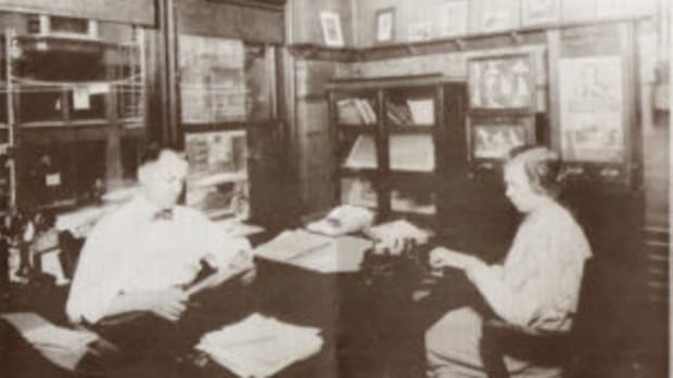 "J. Frank Meyer (left) of ESCO worked from offices on Printers' Row in Chicago. This 1914 photo shows the vending card machines for ""art models"" against the wall. The photo was obtained from Chet Gore and appeared in Bob Schulhof's ""Penny Arcade"" newsletter in 1990."