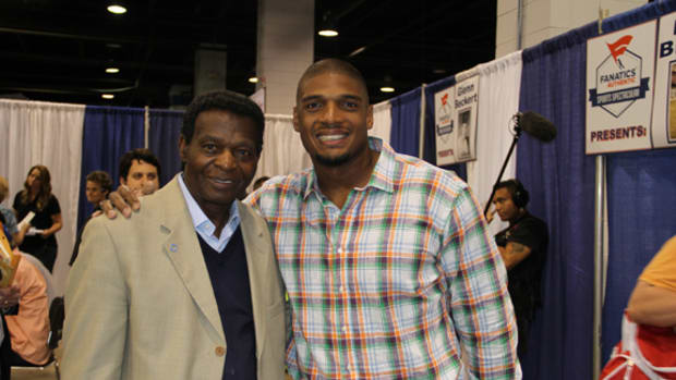 Michael Sam made his first appearance at a sports collectible show, signing at the Fanatics Authentic show in Rosemont, Ill. Among those who reached out to Sam at the event was Lou Brock, left.