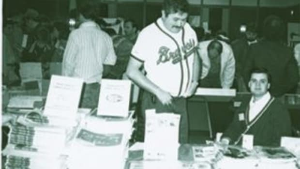 Bob Lemke (standing, wearing a Braves jersey) was an early pioneer in the sports cards hobby. Helping to advance the hobby, Lemke attended many card shows to get Sports Collectors Digest and Baseball Cards magazine into the hands of collectors.