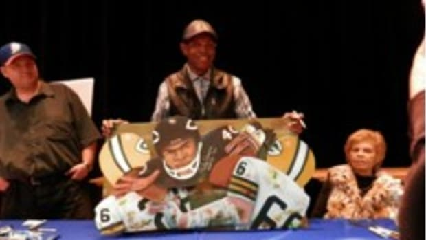 Chicago Bears legend Gale Sayers shows off a one-of-a-kind original piece of artwork for a local artist/fan on the floor of JPRS's Winter Extravaganza Show.