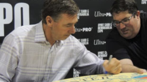 Bernie Nicholls, who played in the NHL from 1981-1999, signs a large piece of memorabilia for a fan at the Toronto Sport Card & Memorabilia Expo. (Hank Davis photos)