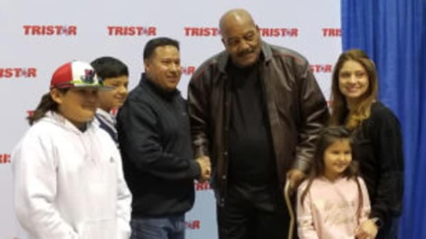 Pro Football Hall of Famer Jim Brown poses for a photo with fans at the 32nd TRISTAR Collectors Show in Houston. (Ross Forman photos)