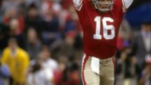 Quarterback Joe Montana #16 of the San Francisco 49ers throw his hands in the air after throwing a touchdown pass during an NFL football game mid circa 1980s at Candlestick Park in San Francisco, California. Montana played for the 49ers from 1979-92. (Photo by Focus on Sport/Getty Images)