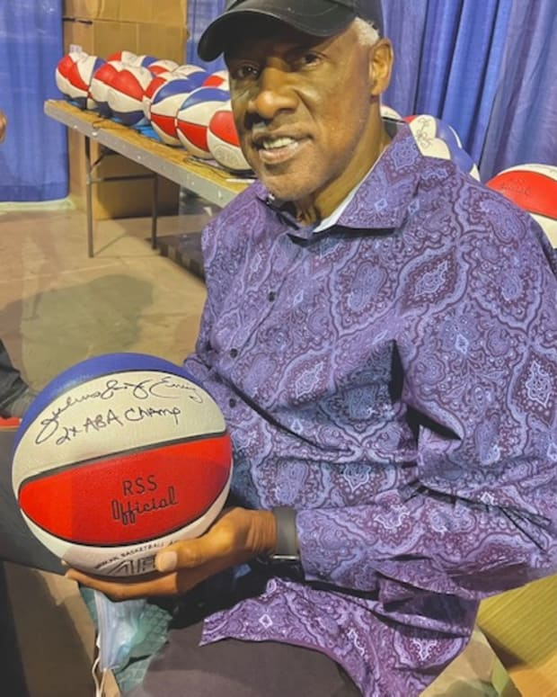 ABA and NBA great Julius Erving with a signed ABA ball being sold by Lana Sports.