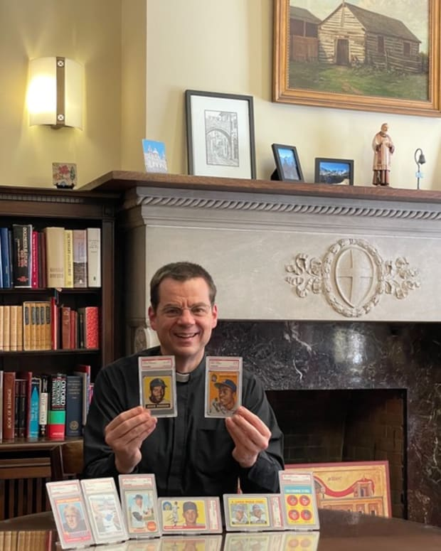 Father John Ubel and his baseball card collection.