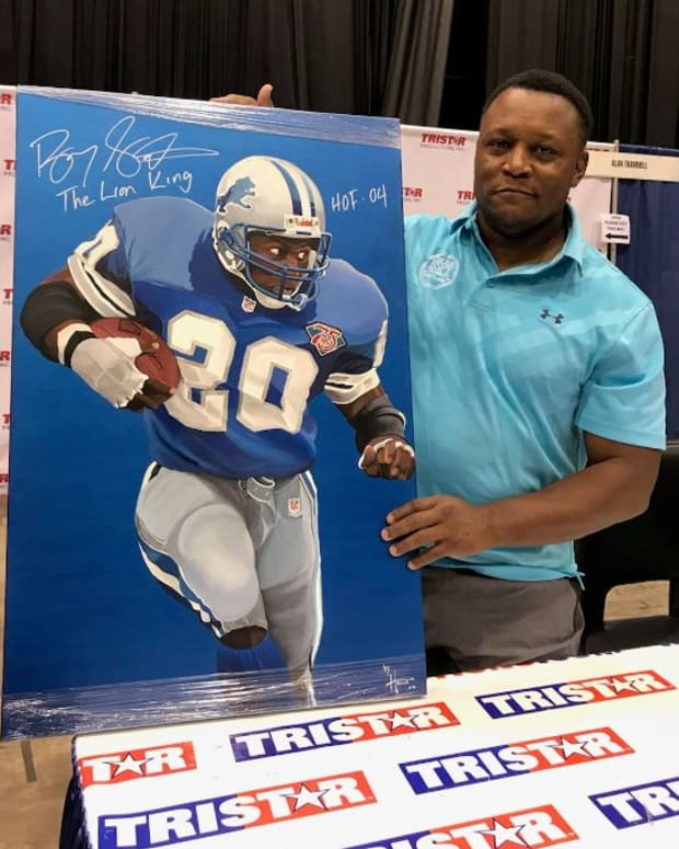 Hall of Famer Barry Sanders shows off a signed poster at the 2019 National.