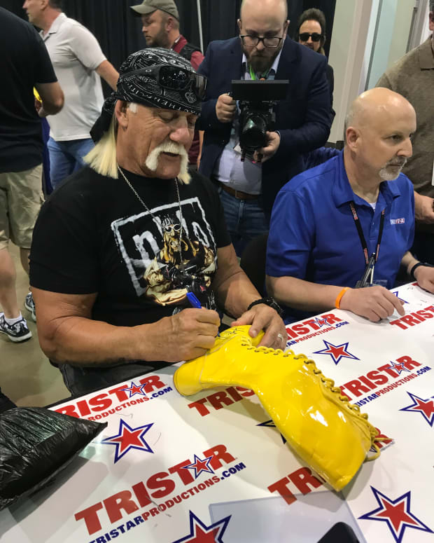Hulk Hogan signs one of his famous yellow boots.
