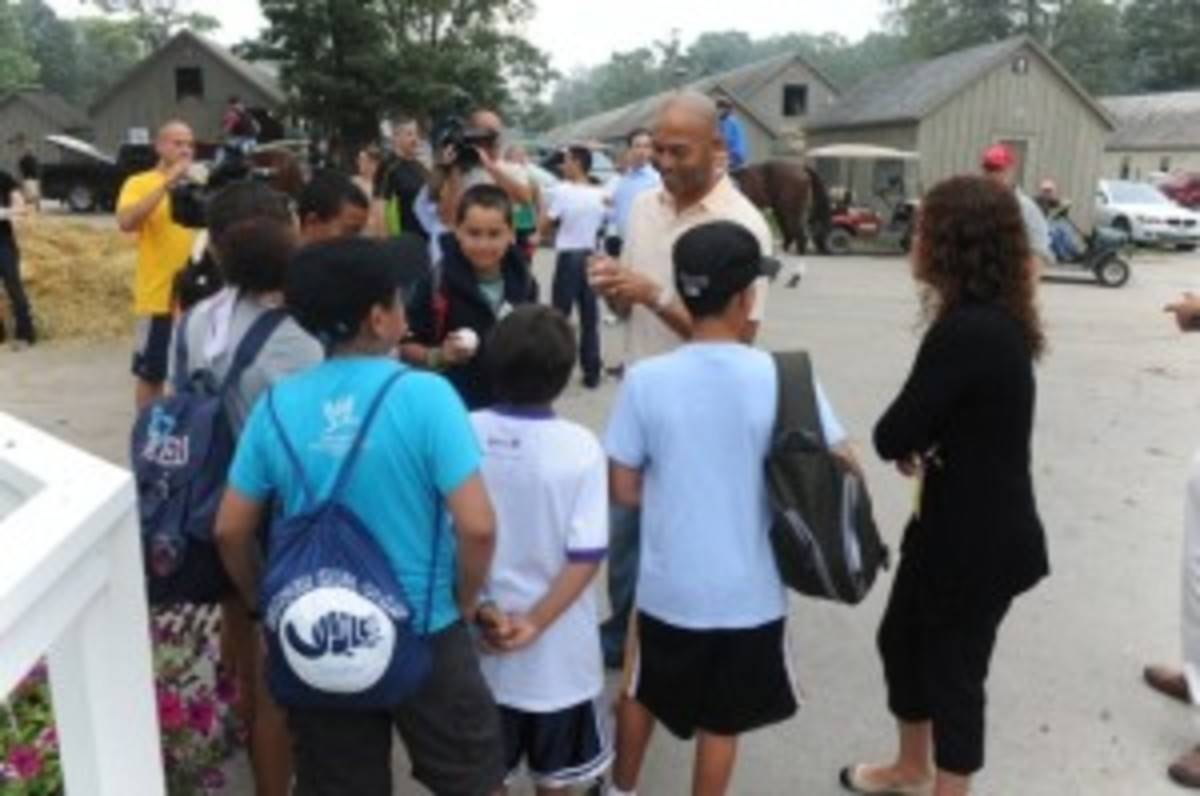 Mariano Rivera signs baseballs for children of backstretch workers who are attending the New York Race Track Chaplaincy Summer Enrichment Program during a tour of the backstretch at Saratoga Race Course on Aug. 10. The camp attendees are children of Saratoga stable workers. Each year, the New York Race Track Chaplaincy organizes summer camps for 32 children during their time in Saratoga.