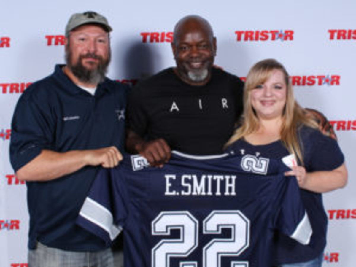 Football Hall of Famer Emmitt Smith shares a photo with a couple of Dallas Cowboys fans. (Ross Forman)