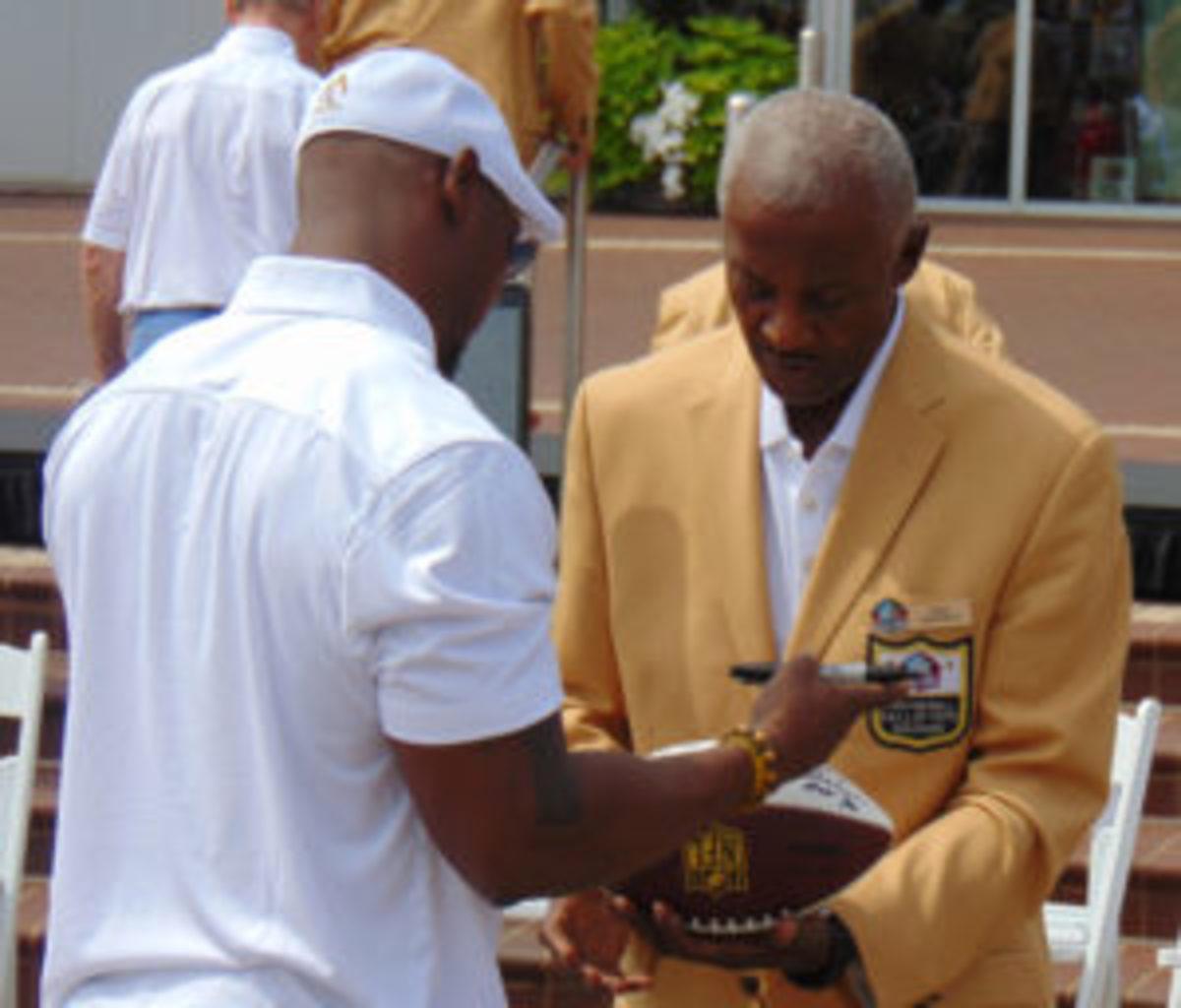 Brian Dawkins (left) signs a football for Hall of Famer Paul Warfield after the reunion photo. (Robert Kunz photo)