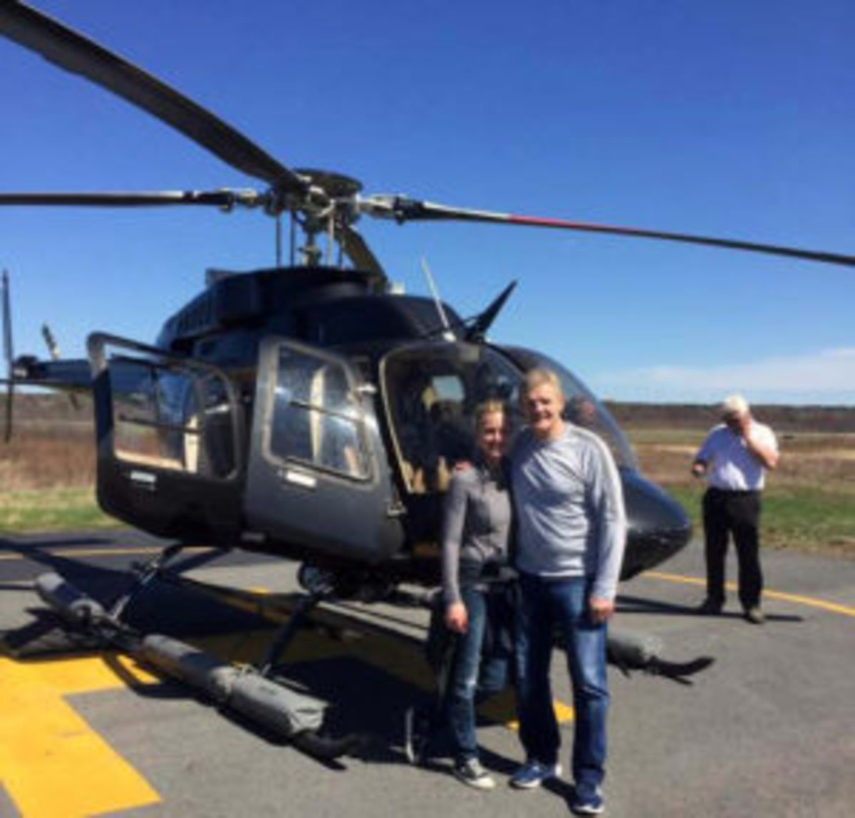 Former Boston Bruins hockey star Chris Nilan (right) in front of the helicopter that was flown by former Montreal Canadiens star Guy LaFleur to a Cardboard Promotions' show. Both Nilan and LaFleur were autograph signers at the show.