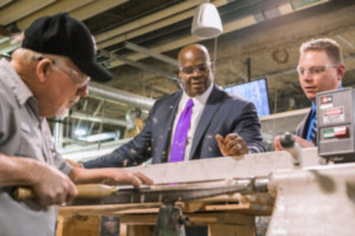 Louisville Slugger Museum & Factory employee, Mike Dennison, shows Frank Thomas how the company used to make bats by hand on a lathe.