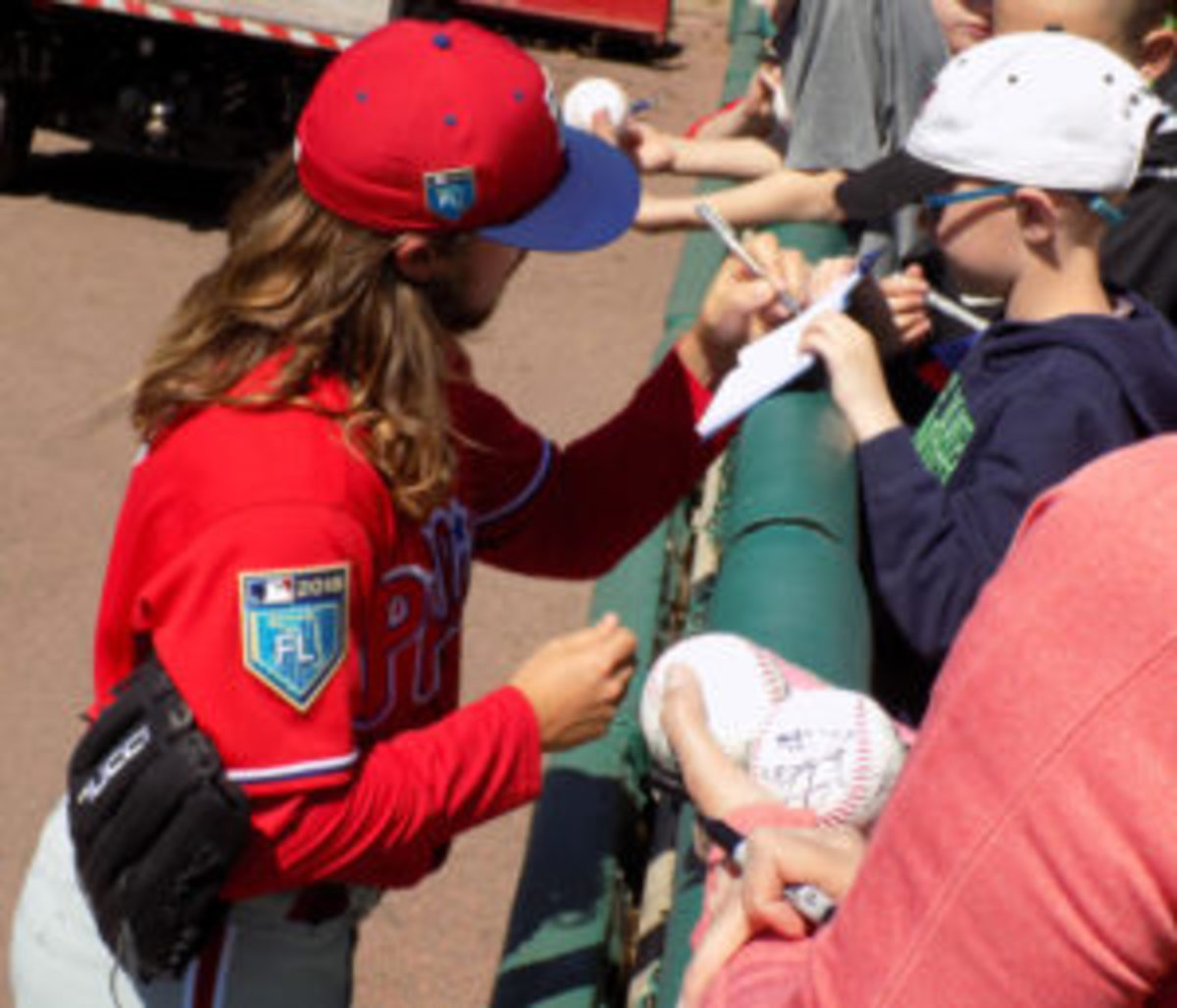 A Philadelphia Phillies player signs an autograph for a young fan at a Spring Training game. Players usually sign autographs along the fences near the dugout. (Barry Blair photos)