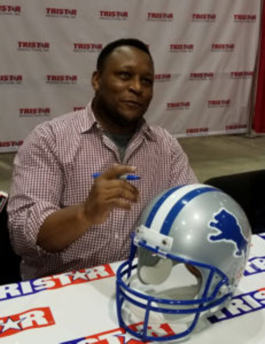 Football Hall of Famer Barry Sanders signs a helmet at the Tristar Collectors Show in Houston.