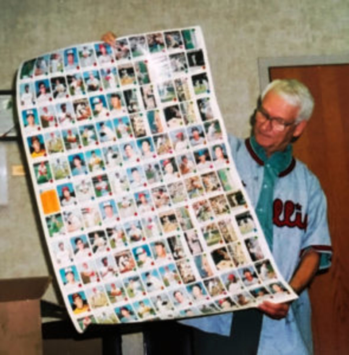 Gar Miller at a speaking engagement, showing off an uncut 1973 Topps sheet, while wearing an autographed Ashburn jersey. (Photo courtesy Gar Miller)
