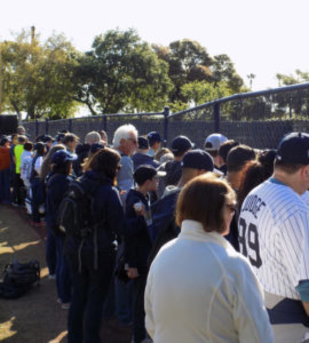 Fans and collectors wait for a New York Yankees workout to end for their chance to get autographs.
