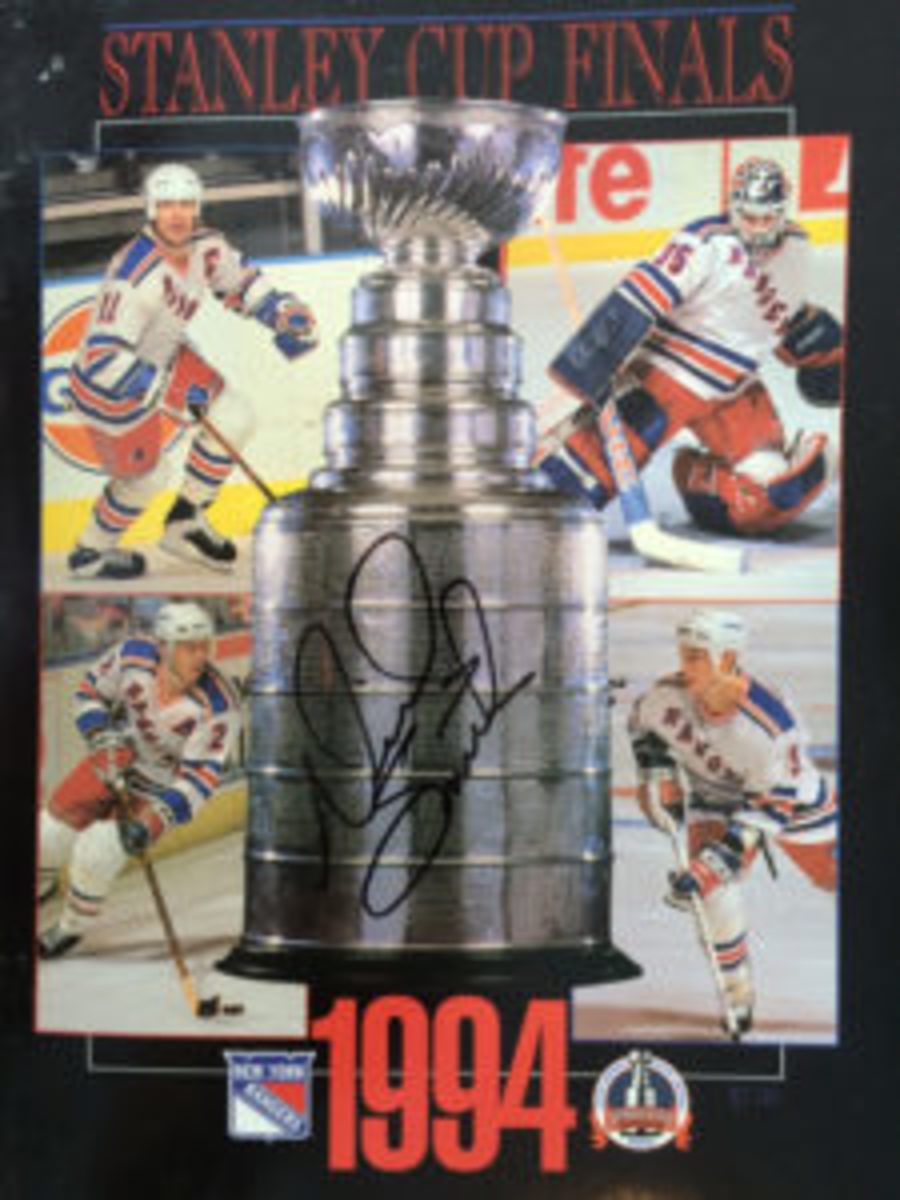 A program cover from the 1994 Stanley Cup Finals autographed by Rangers General Manager Neil Smith. The players, clockwise starting from top left, are Mark Messier, Mike Richter, Brian Leetch and Adam Graves.