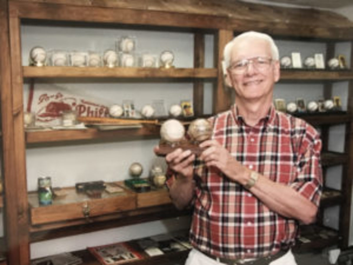 Gar Miller in 2002 in his mini-museum with some of the display items: autographed bats and balls. (David Hunsinger photo)