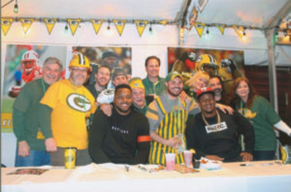A group of fans who attended the PackerPalooza event have their photo taken with Green Bay Packers players Jayrone Elliott (left) and Mike Daniels (right).