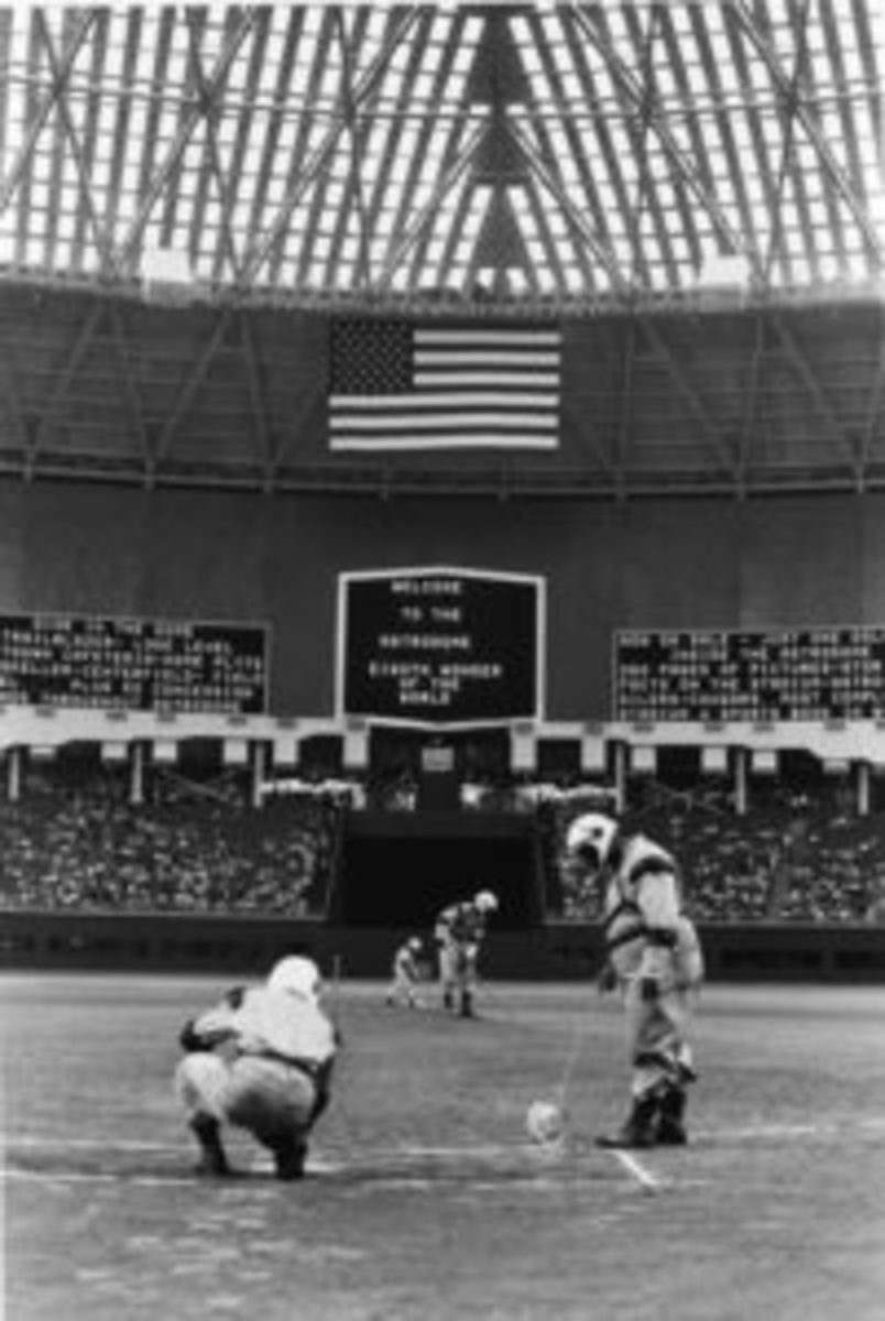 Groundskeepers are forced to wear 'futuristic' spacesuit uniforms as they prepare the diamond for the first game in the Astrodome, Houston, Texas, April 12, 1965. The dome, as seen here, had a translucent roof to allow the grass to grow but glare caused the panes to be painted over, which in turn caused the grass to die. Eventually Monsanto invented AstroTurf, the first and most famous artificial grass replacement. (Photo by Robert Riger/Getty Images)