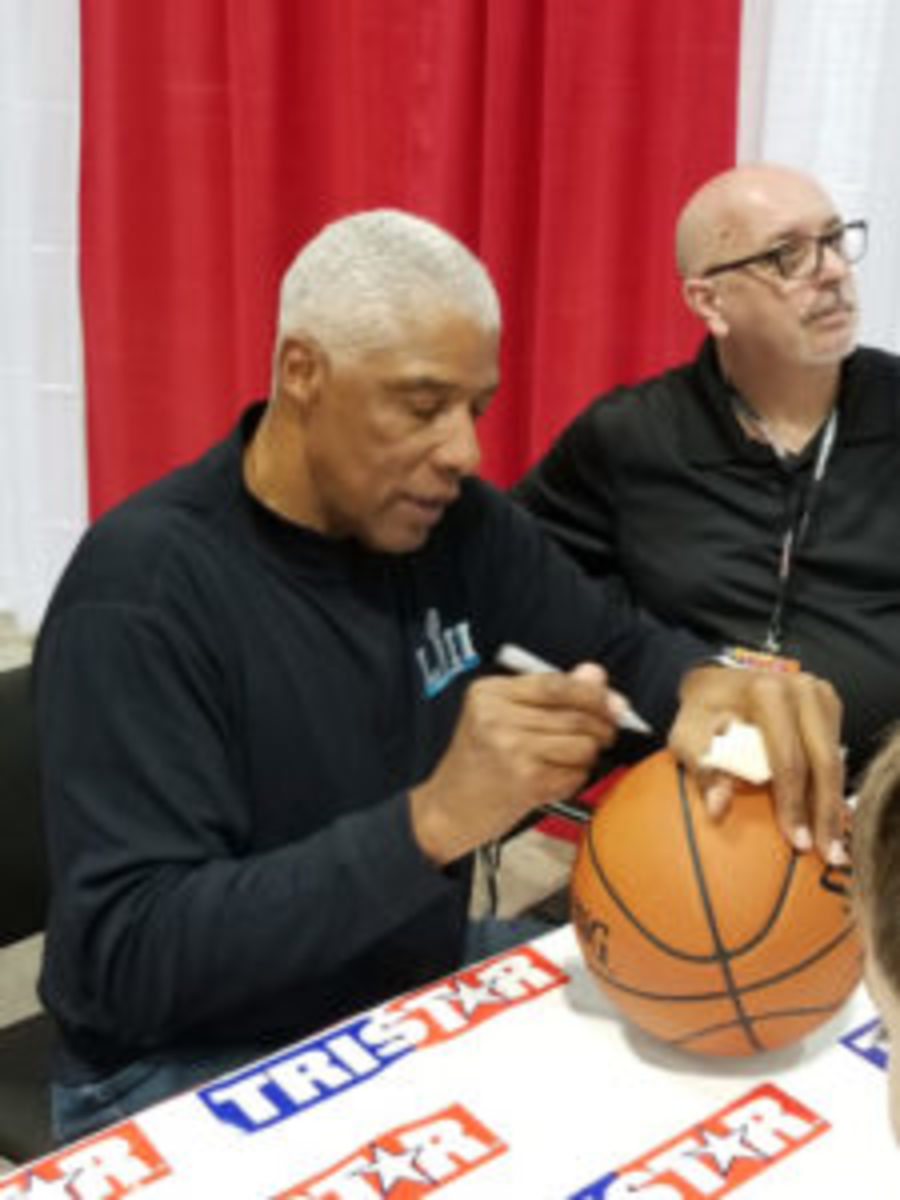 Basketball Hall of Famer Julius Erving signs a basketball at the Tristar Collectors Show in Houston.