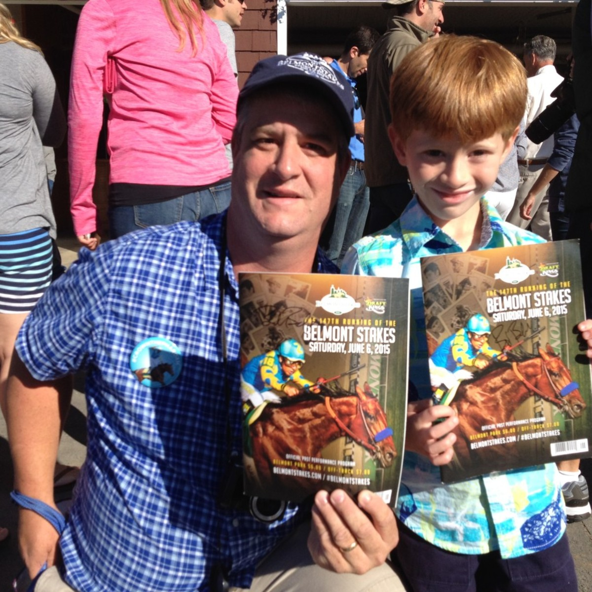 Joe Deucker and his son, Jack, show off Belmont Stakes programs signed by American Pharoah trainer Bob Baffert.