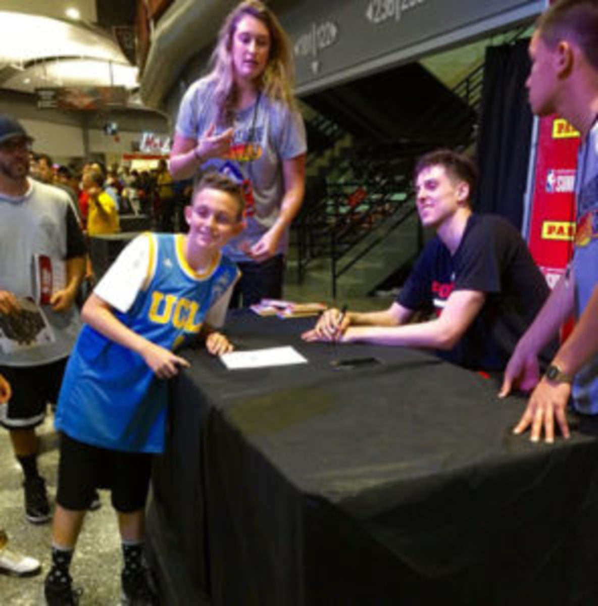 Zach Collins of the Portland Trailblazers takes time at the autograph table to pose for a photo with a fan.