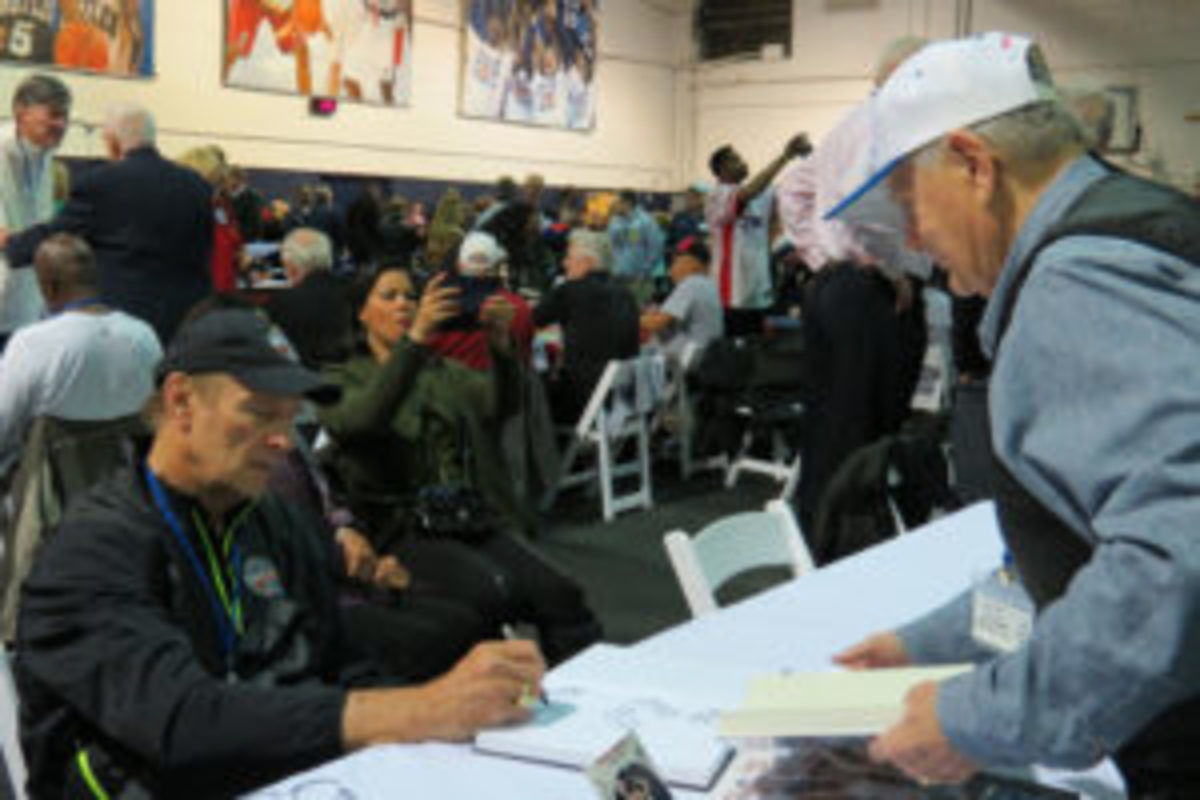 """Rick Barry signs a book for Lloyd """"Pink"""" Gardner, former travel secretary, equipment manager and trainer for the Kentucky Colonels."""