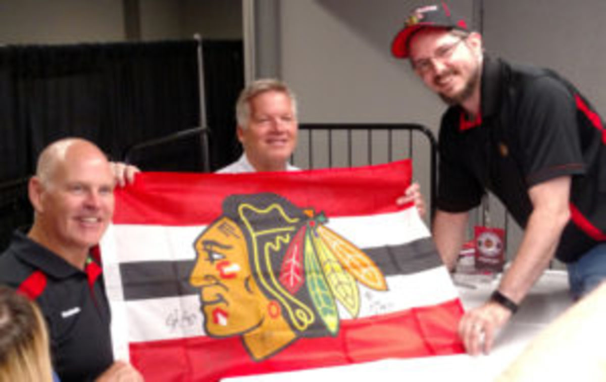 Retired Blackhawks players, and current team broadcasters, Troy Murray (left) and Steve Konroyd (center) pose with a fan.