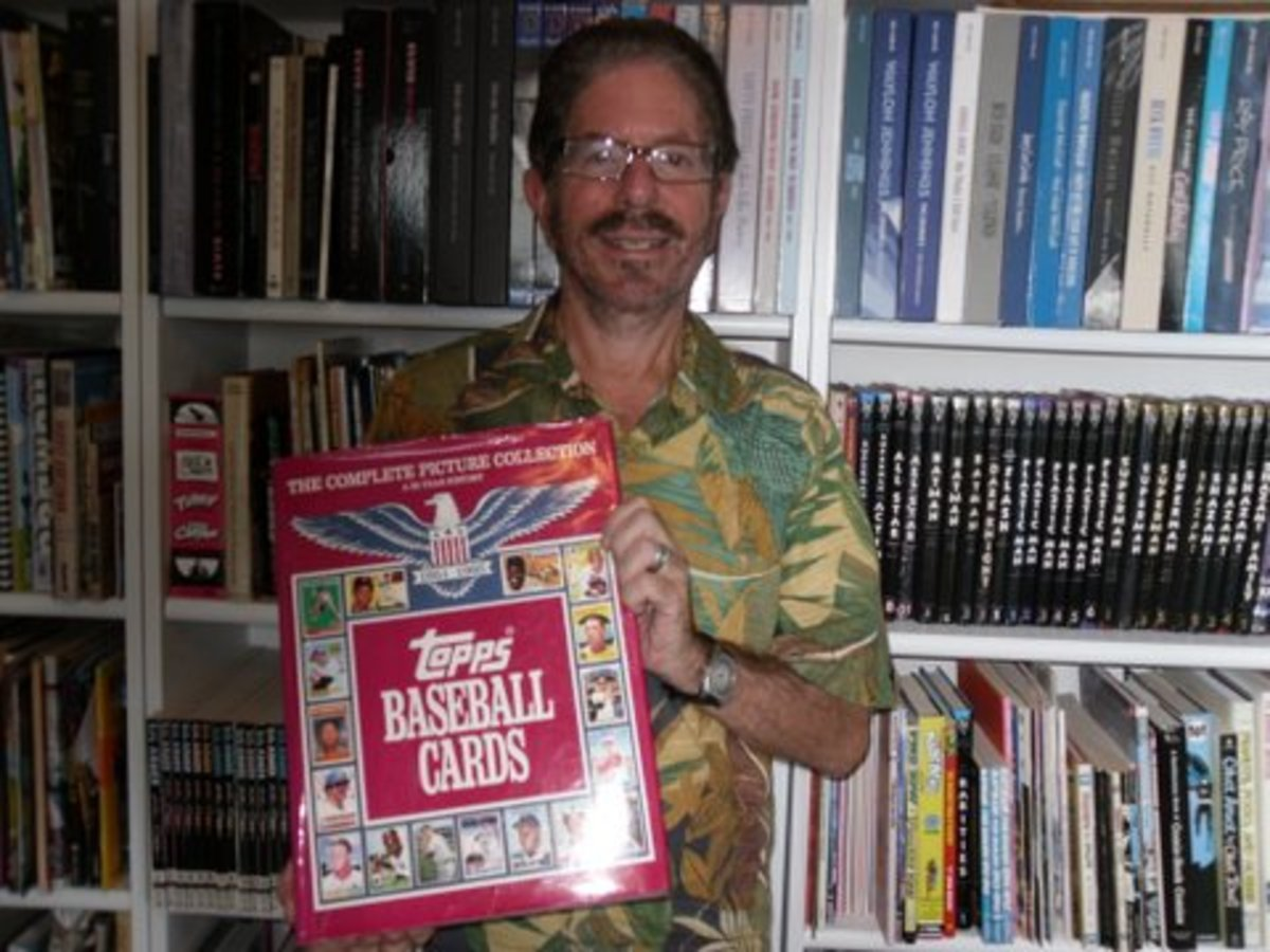 Len Brown holding the book Topps Baseball Cards.