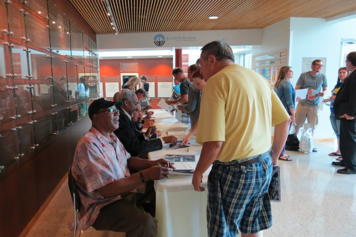 George McGinnis (seated) chats with a fan during the Dropping Dimes Foundation's Tip-Off Event and Fundraiser, while Darnell Hillman (seated to McGinnis' left) signs a photo for another fan.