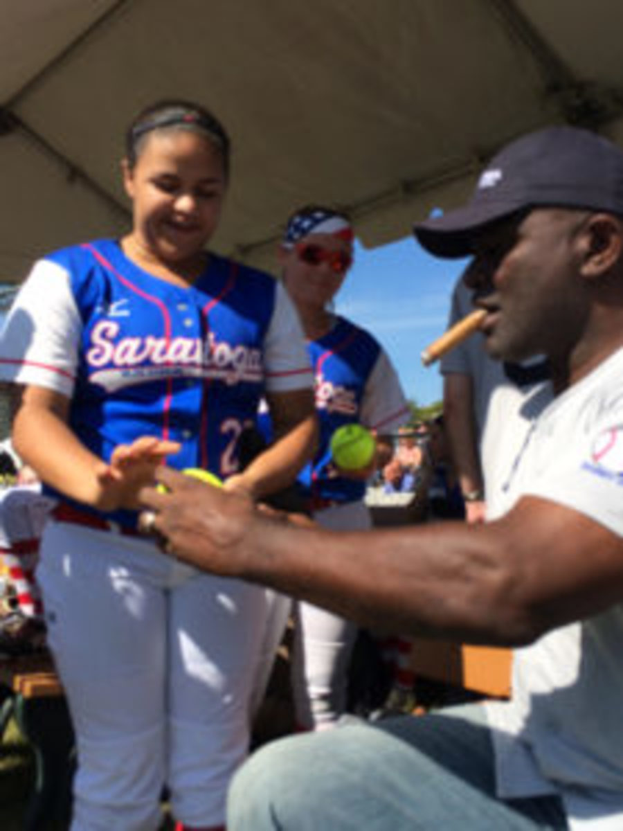 Football Hall of Famer Lawrence Taylor signs a baseball for a young fan.