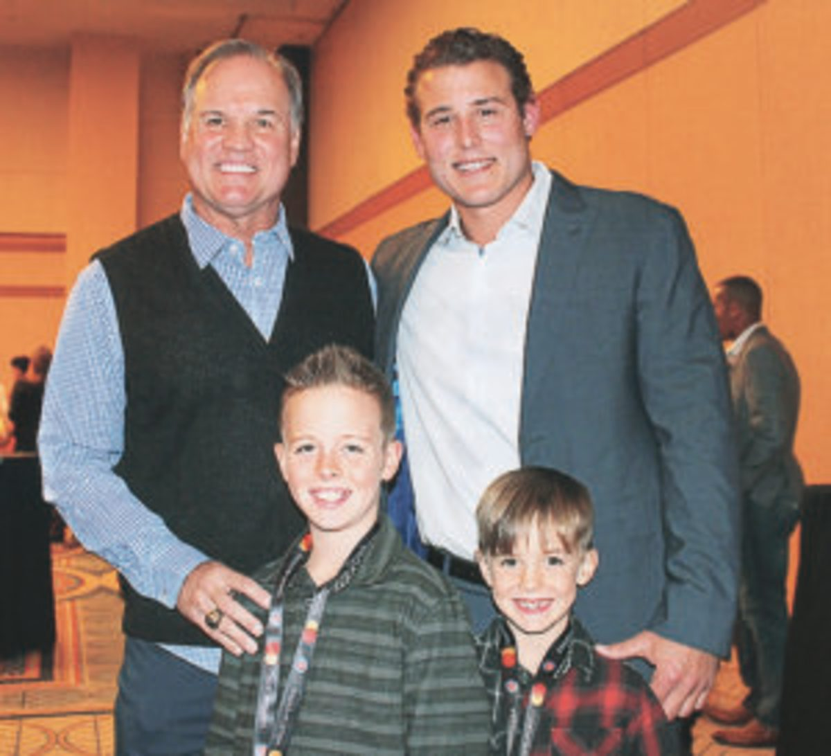 Former Cubs player Ryne Sandberg (left) and current Cubs player Anthony Rizzo pose for a photo with Sandberg's grandsons.