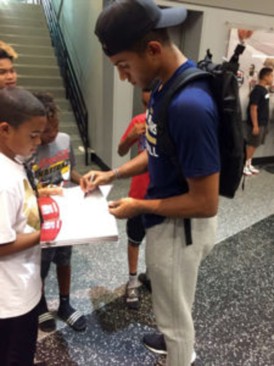 Frank Jackson, a first round draftee for New Orleans, signs autographs for fans in the concourse at the NBA Summer League held in July.