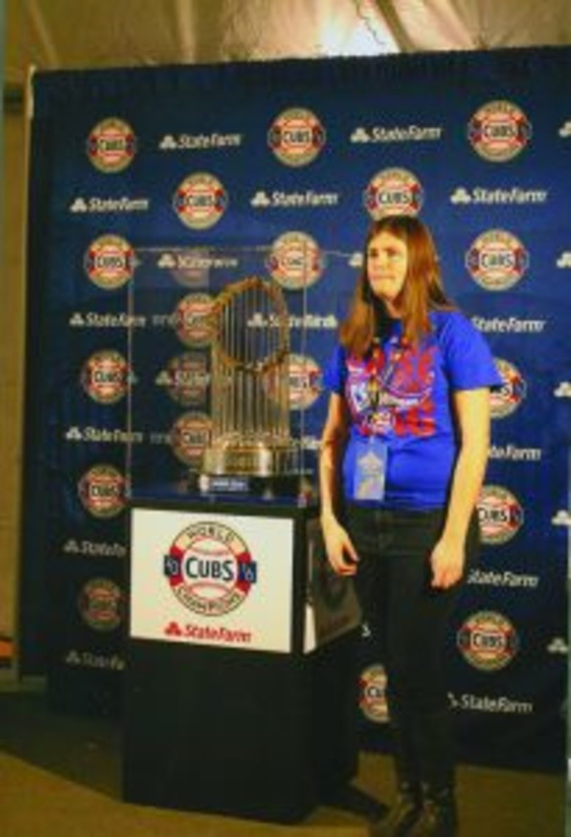 A fan poses with the World Series Trophy, which was on display at the Cubs Convention.