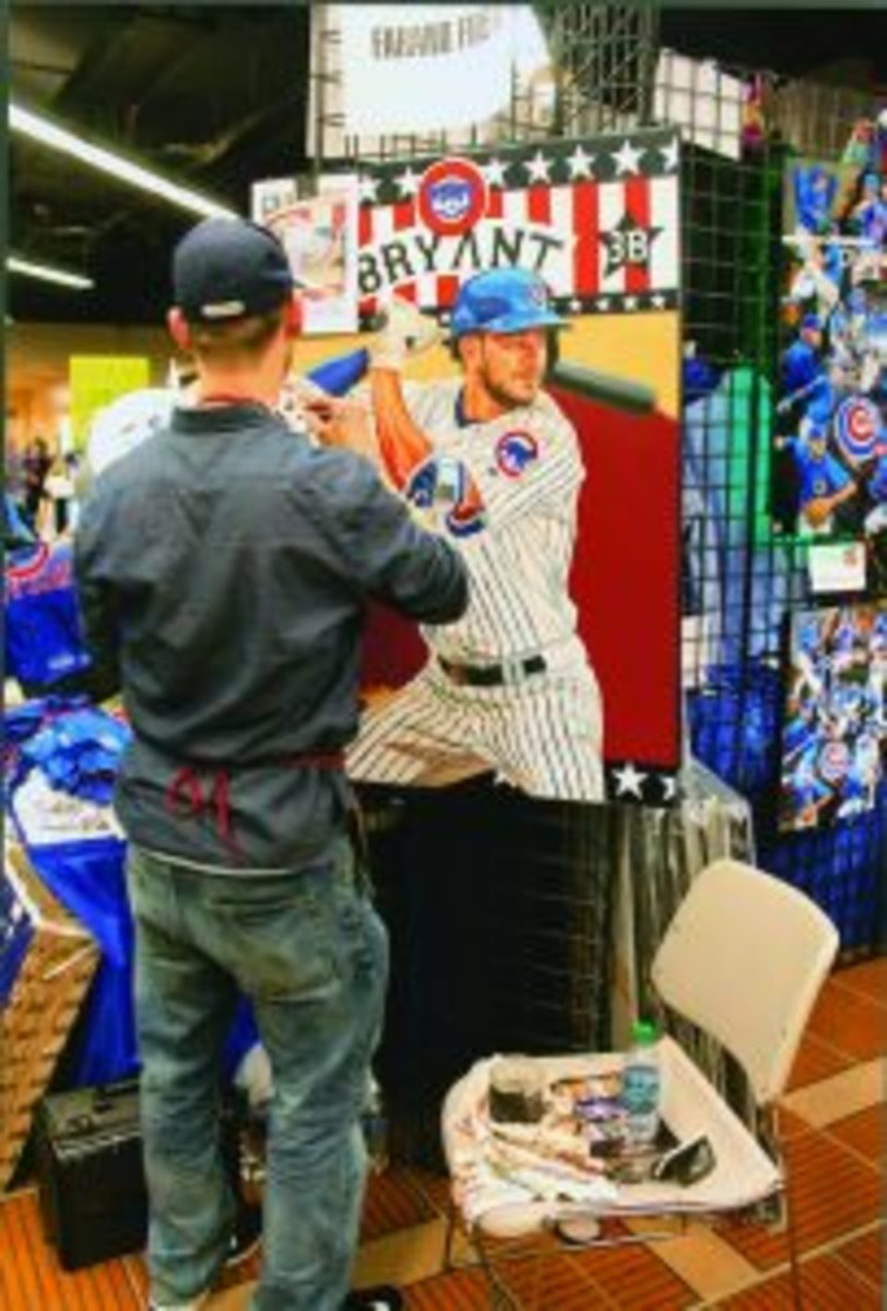 Artist Justyn Farano executing a painting of Kris Bryant in the vendors area.