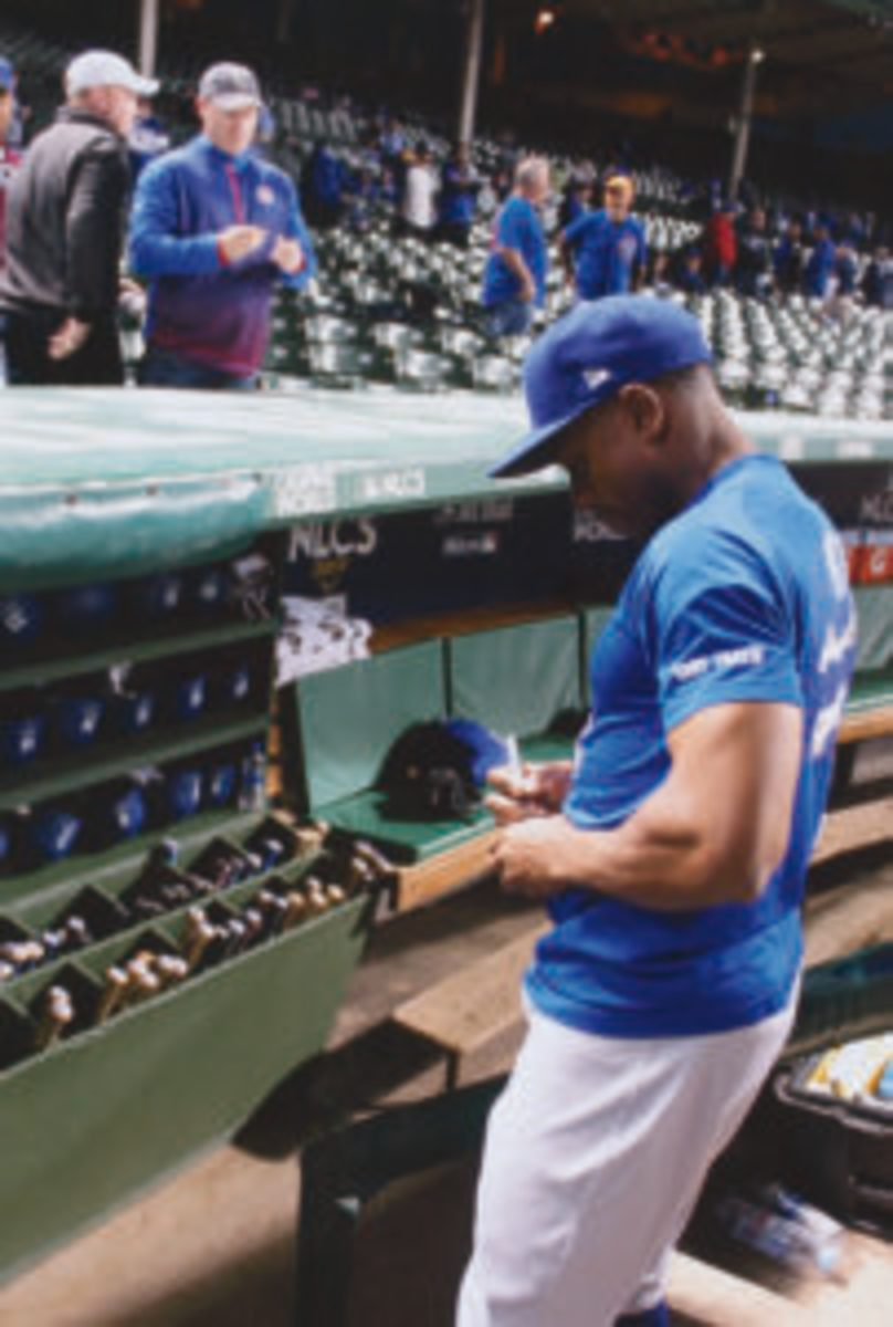 Curtis Granderson signs an autograph for a fan prior to a National League Championship Series game at Wrigley Field.