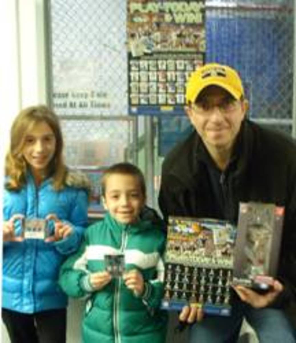 Frank Rosato with his son Michael and daughter Emily showing off the prizes they won at Attack of the Baseball Cards in the Panini NFL Player of the Day promotion.