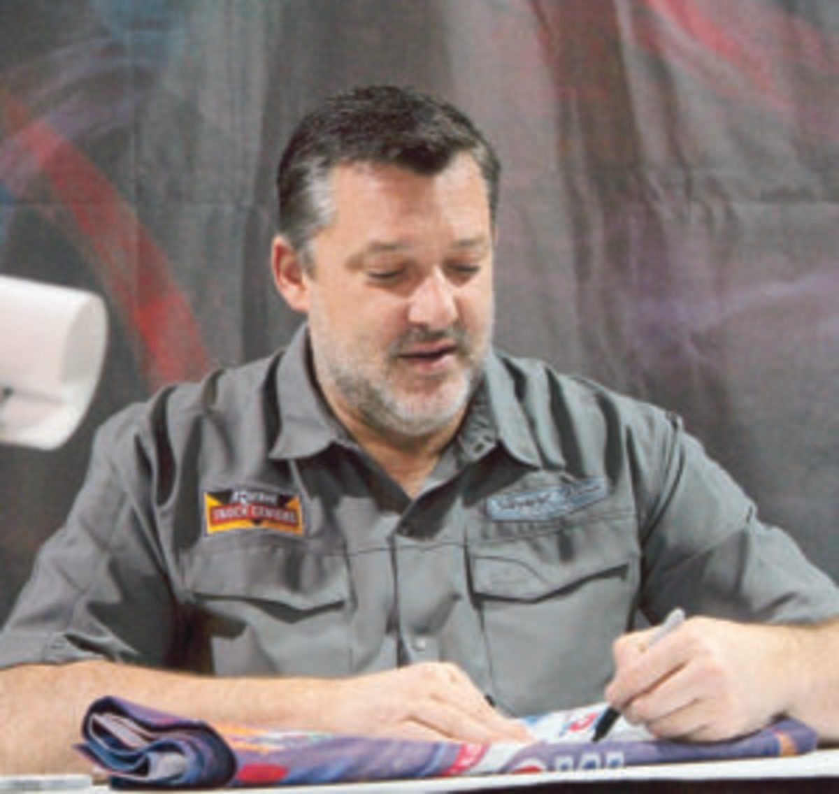 Former NASCAR star Tony Stewart signs autographs at the 2019 Chicago World of Wheels show.