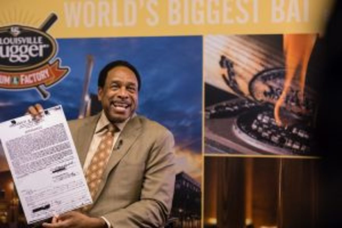 Dave Winfield holds up an enlarged copy of his contract to receive bats from Louisville Slugger.