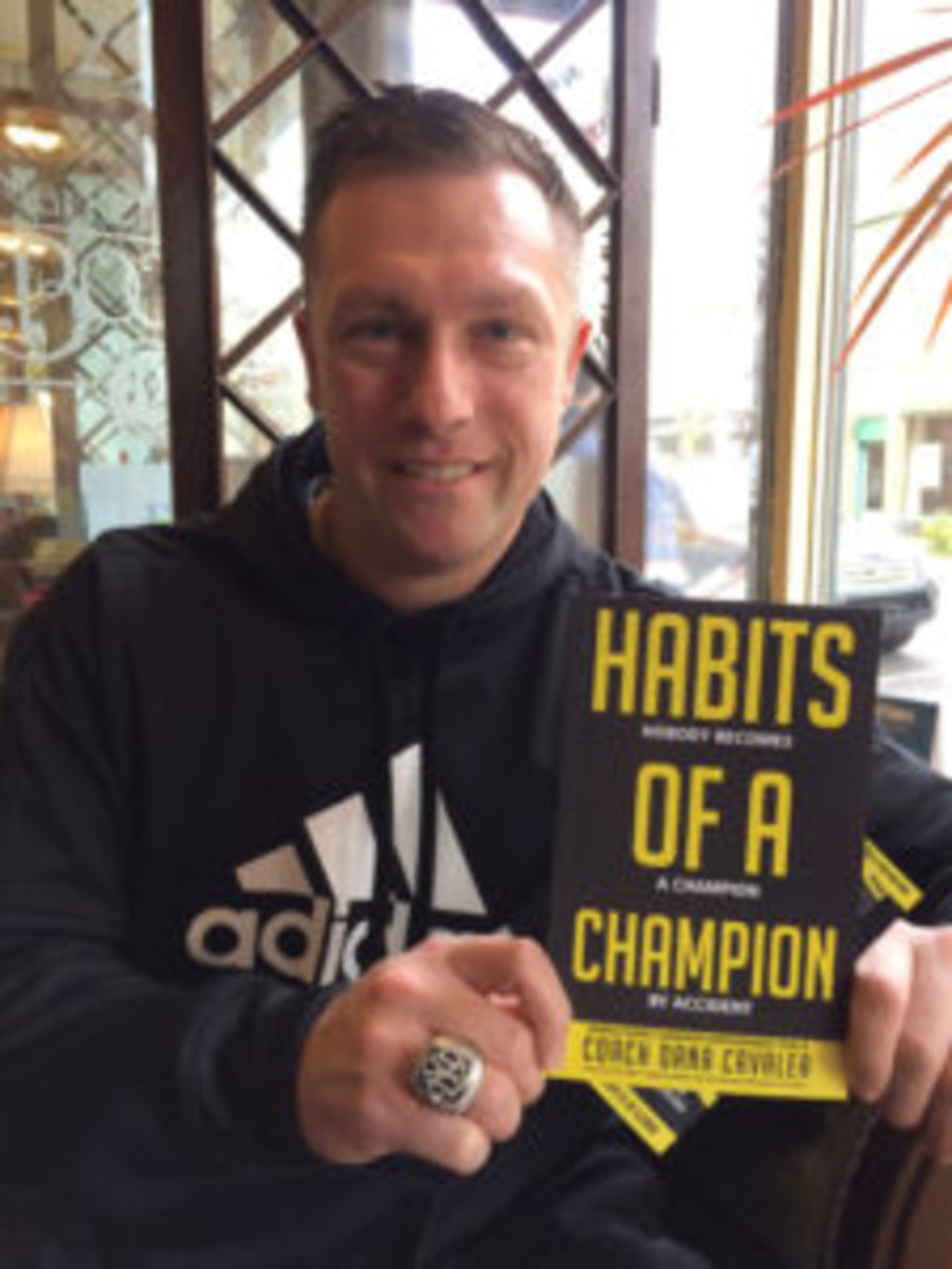 "Dana Cavalea displays a copy of his new book, ""Habits of a Champion."" He's wearing the World Series ring he won with the 2009 New York Yankees. (Paul Post photo)"