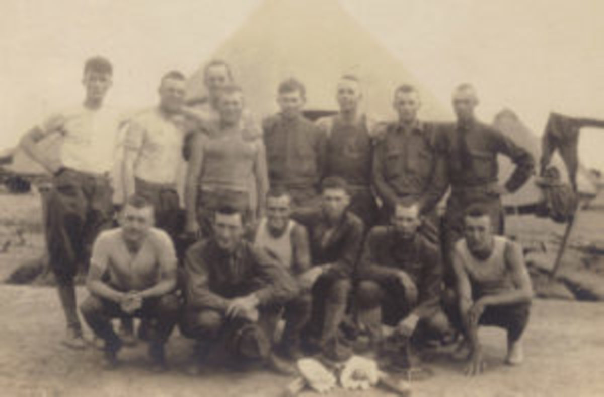 A group of National Guard soldiers gather around some of their baseball equipment for a photograph. The campaign hats and canvas leggings visible in this photograph would disappear and be replaced with more practical cloth caps and puttees after the soldiers arrived in France.