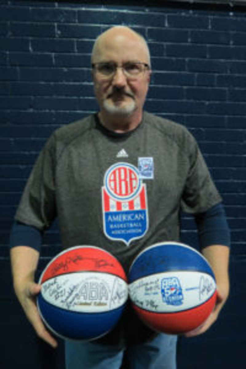 Conrad Brunner, owner of Bruno's Shoebox, a new sports memorabilia store in Noblesville, Indiana, shows off two of the ABA 50th Anniversary commemorative basketballs he had been using to collect autographs.