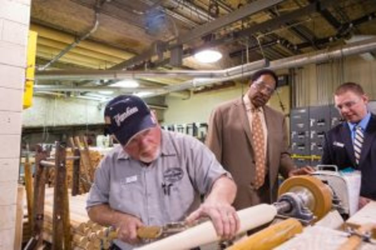 Louisville Slugger Museum & Factory employee, Mike Dennison, shows Dave Winfield how the company used to make bats by hand on a lathe.