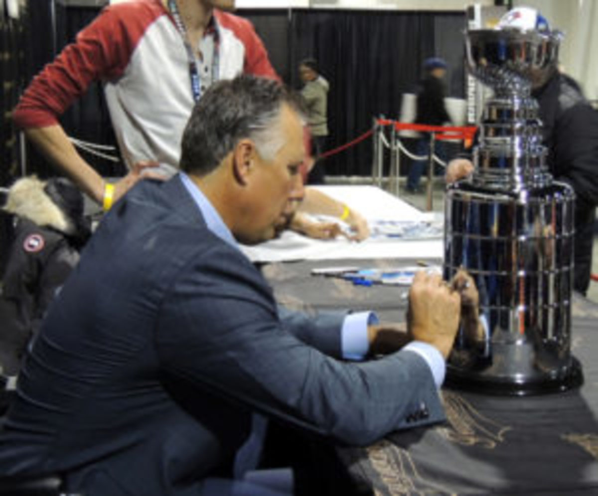 Hockey Hall of Famer Dave Andreychuk signs a replica of the Stanley Cup. (Hank Davis photos)