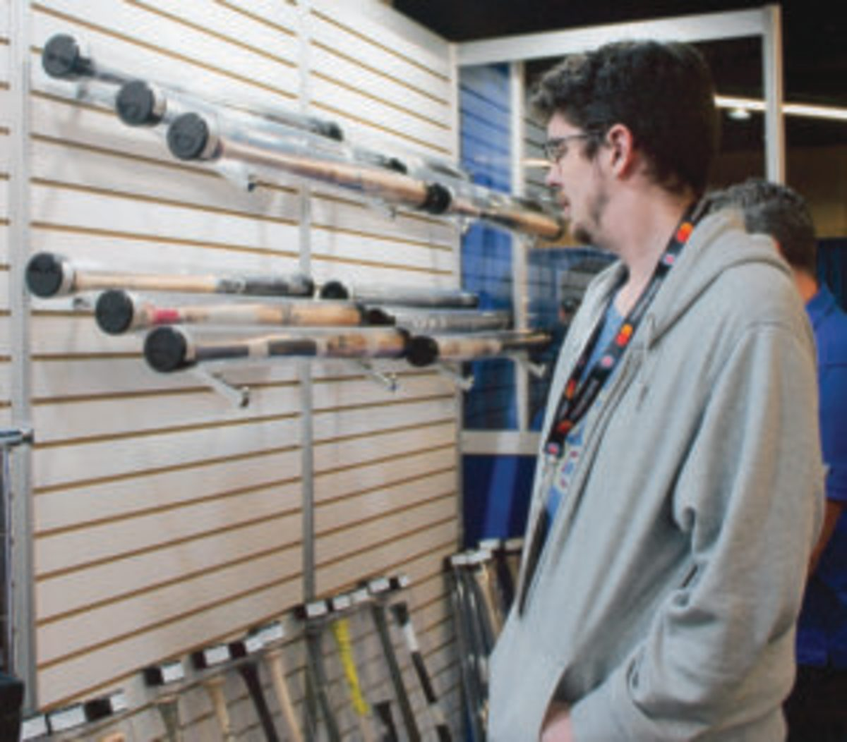 An attendee at the Cubs Convention looks over many game-used bats that were for sale.