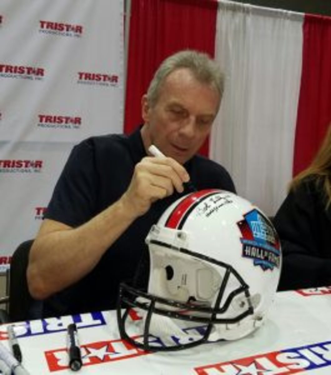 Joe Montana signs a Football Hall of Fame helmet at the 31st annual Tristar Collectors Show in Houston earlier this year. (Ross Forman photo)